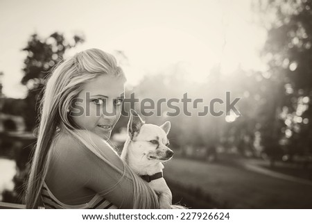 Little chihuahua and blonde girl in the park - stock photo