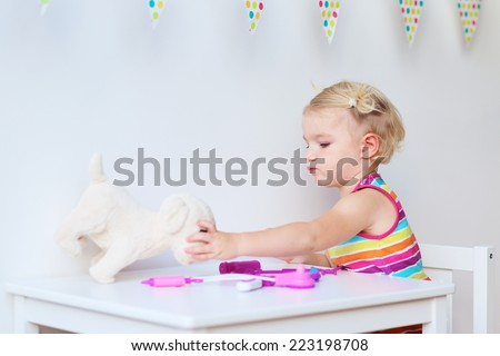 Little child, adorable blonde toddler girl, playing doctor role game and treating her puppy using different medical tools sitting at small white table in playroom at home, school or kindergarten - stock photo