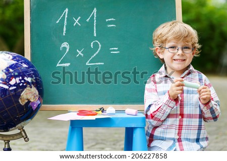 Little child at blackboard practicing mathematics, outdoor school or nursery. Back to school concept
