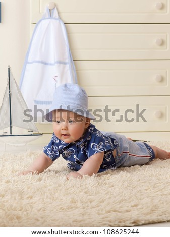 little child baby boy lying on the floor carpet indoors in baby room hat fashion clothing - stock photo