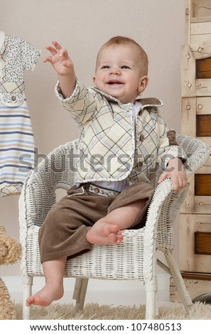 little child baby boy sitting on the chair indoors in baby room smiling happy