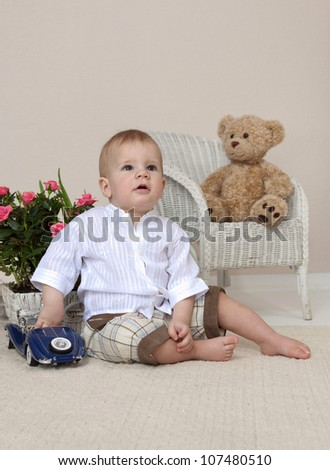 little child baby boy sitting on the floor indoors in baby room playing with toy car - stock photo