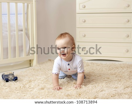 little child baby boy sitting on the floor on the carpet indoors in baby room smiling - stock photo