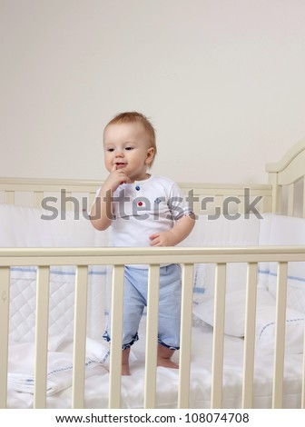 little child baby boy standing in bed indoors in baby room finger in the mouse - stock photo