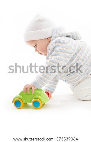 little child baby caucasian playing with car warm clothing studio shot isolated on white