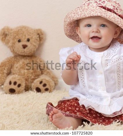 little child baby girl sitting on the chair indoors in baby room smiling teddy bear lamp - stock photo