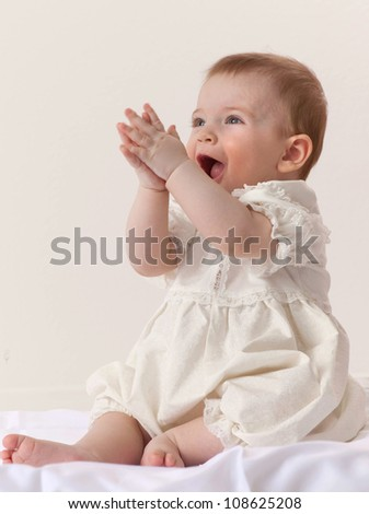 little child baby girl sitting on the chair indoors in beautiful dress fashion smiling studio shot
