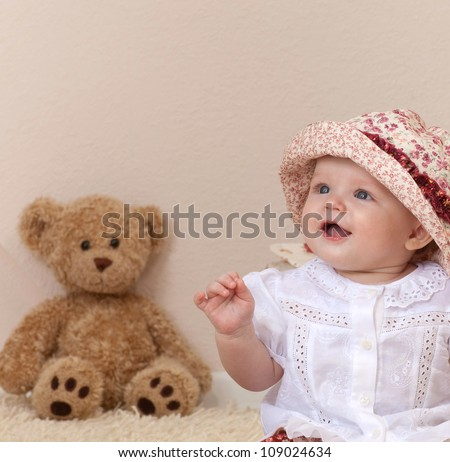 little child baby girl sitting on the floor carpet  indoors in baby room smiling teddy bear lamp - stock photo