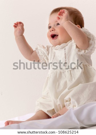 little child baby girl sitting on the floor indoors studio shot dress fashion smiling