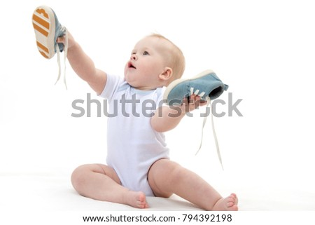 little child baby s isolated on white studio shot sitting playing with shoes