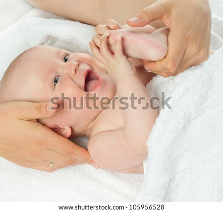 little child baby smiling closeup portrait lying on white towel studio shot face positive happy mother's hands - stock photo