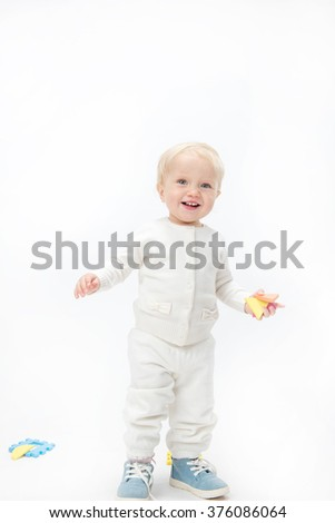 little child baby smiling playing with puzzles warm clothing isolated on white studio shot - stock photo