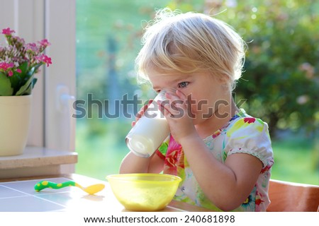 Little child, blonde curly toddler girl, enjoys healthy breakfast eating oatmeal porridge and drinking milk from glass sitting in high chair at bright sunny kitchen next to big garden view window - stock photo