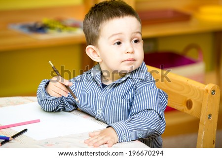 Little child boy drawing with colorful pencils in preschool at the table in kindergarten - stock photo