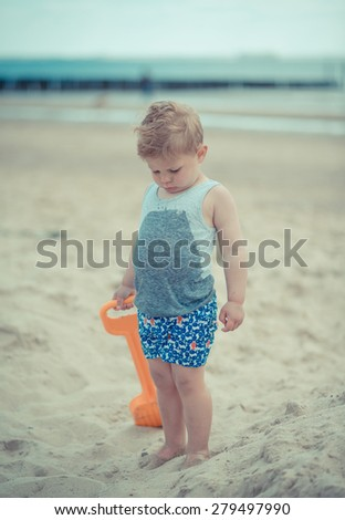 little child boy is upset on the beach because of his wet shirt - stock photo