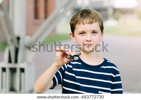 Little child boy playing with fidget spinner outdoors - popular plastic toy