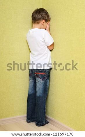 Little child boy wall corner punishment standing - stock photo