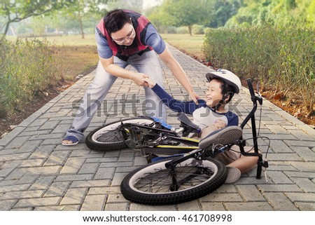 Little child crying after crashing from the bike and helped by his dad on the road