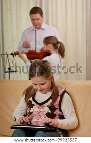 Little child (cute girl) is playing with tablet at home while her father is teaching another daughter playing violin