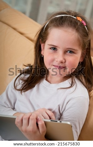 Little child (cute girl) playing with tablet at home sitting on sofa - stock photo