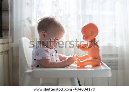 Little child, cute toddler girl having fun playing at home with her doll,playing with baby doll singing doll out of the cup, takes care of  doll, casual lifestyle photo series in real life interior, - stock photo