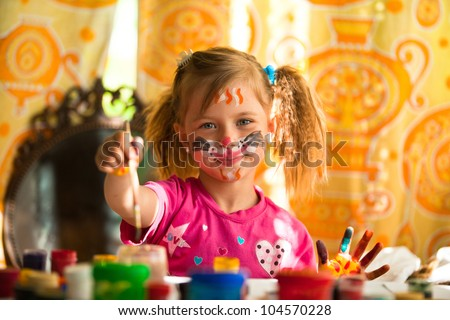 Little child, drawing paint with paint of face. - stock photo