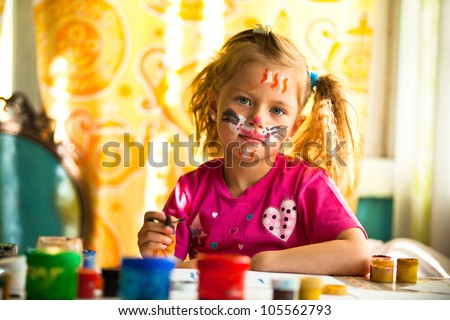 Little child, drawing paint with paint of face