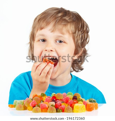 Little child eating candies on a white background - stock photo