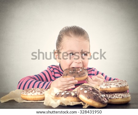 Little child eating sweet chocolate donuts,selective focus