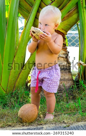 Little child eats coconut - stock photo