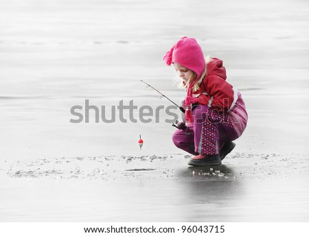 Little child fishing on a frozen lake in winter. - stock photo