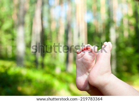 Little child gets his feet into the fresh air in a summer forest