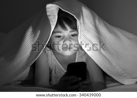 Little child (Girl age 5-6) play on smart phone in bed under the covers at night. Front view, copy space - stock photo