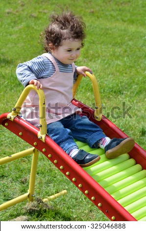 Little child (girl age 1-2) sliding on a slide in a home playground. - stock photo