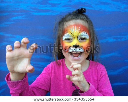 Little child (girl age 5-6) with lion face painting roaring like a lion. - stock photo