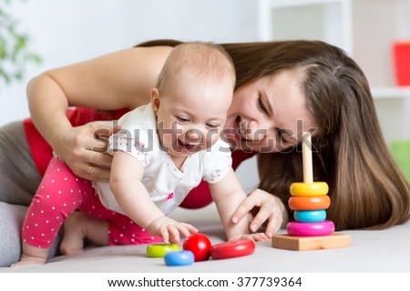 little child girl and her mommy play with color toys at home - stock photo