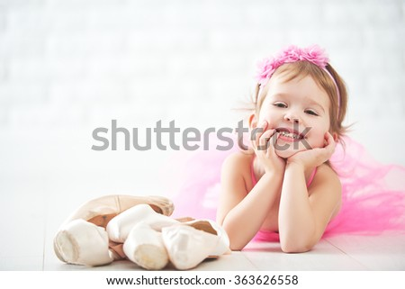little child girl dreams of becoming  ballerina with ballet shoes and pointe shoes in a pink tutu skirt  - stock photo