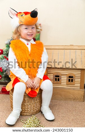 Little child girl dressed in fox suit near Christmas tree. The concept of New Year and holiday - stock photo