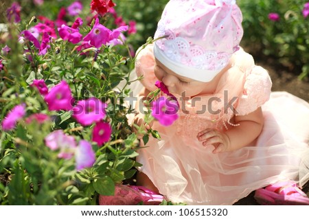 Little child girl enjoy aroma of the flower