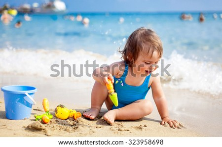 Little child girl in blue swimsuit is playing on the beach near blue sea - stock photo