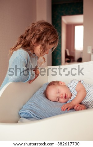 Little child girl looking at sleeping baby boy in room. Childhood. Calmness.