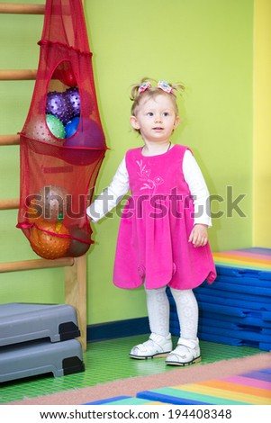 Little child girl playing with ball in kindergarten in Montessori preschool Class. - stock photo