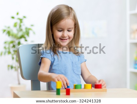 little child girl playing with educational toys - stock photo