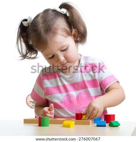 little child girl playing with puzzle toys isolated