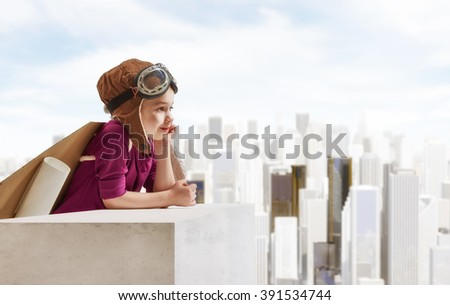 Little child girl plays astronaut. Child looking at city. Child in an astronaut costume plays and dreams of becoming a spaceman. - stock photo