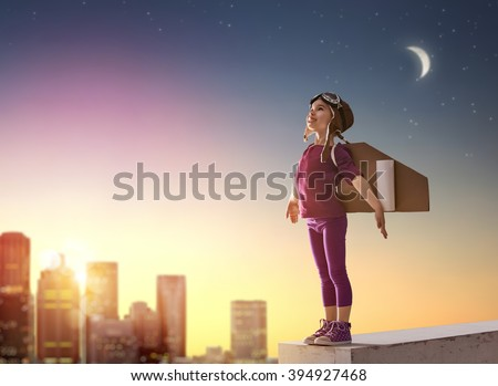 Little child girl plays astronaut. Child on the background of sunset sky. Child in an astronaut costume plays and dreams of becoming a spaceman. - stock photo
