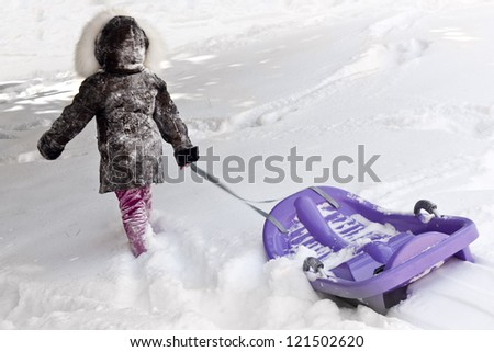 Little child girl pulling his sled in the winter time - stock photo