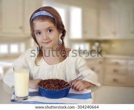 Little child girl siting at the table at the kitchen and eating her corn breakfast. - stock photo