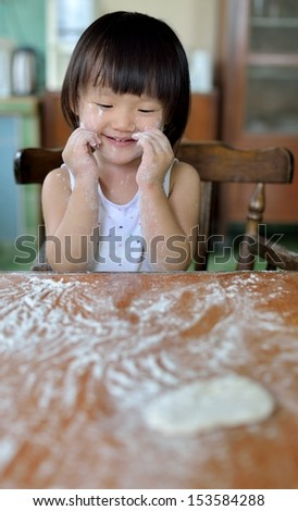 Little child girl sitting at table and playing with dough and flour  - stock photo