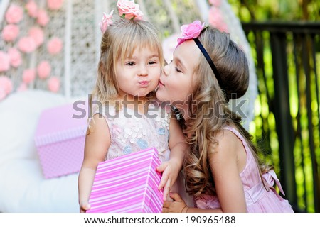 little child give a birthday gift box to her friend  - stock photo